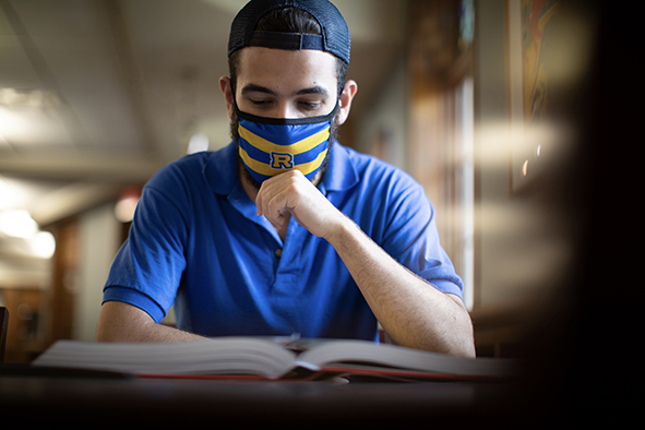 Rollins student at desk with a mask on