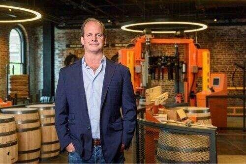 Campbell Brown standing in front of bourbon barrels.