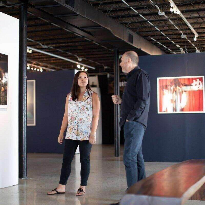 A professor and student walk through a large art gallery.