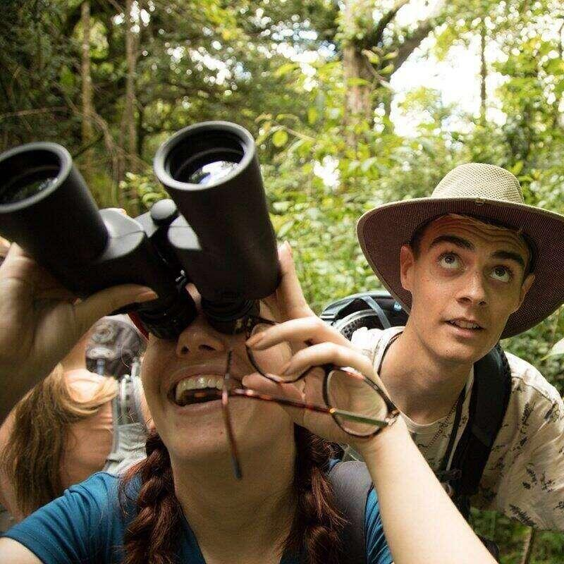 An environmental science student looks through binoculars.