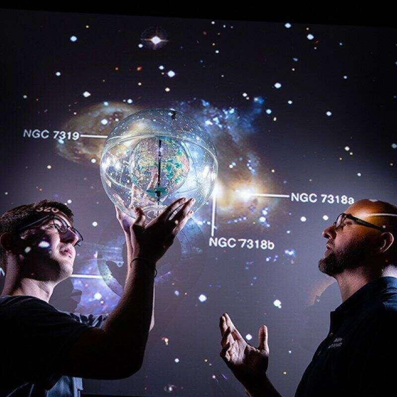 A student and professor study a representation of the night sky.