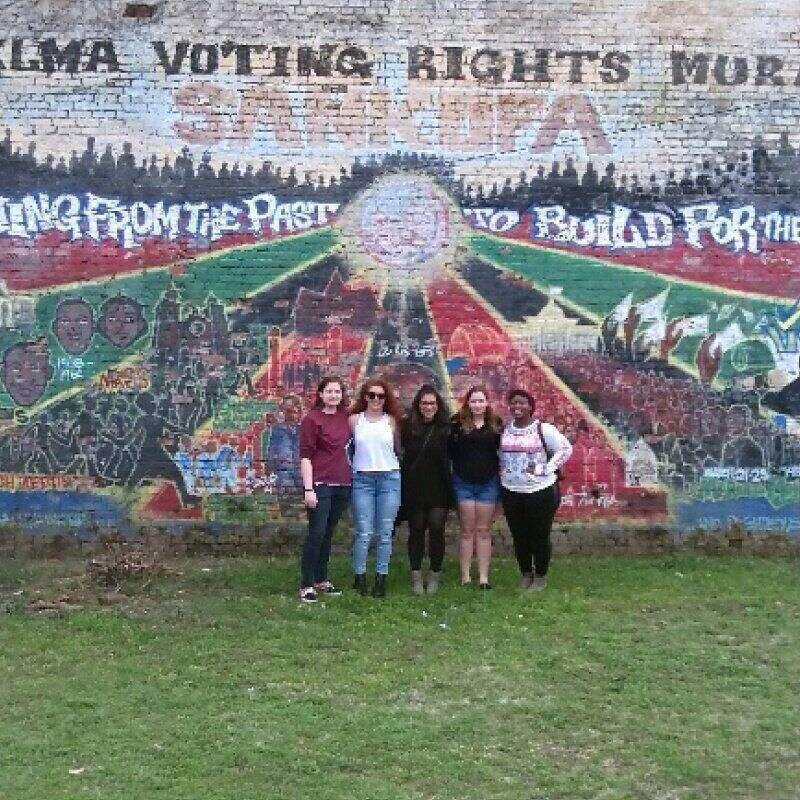 Students pose for a picture in front of a large mural.