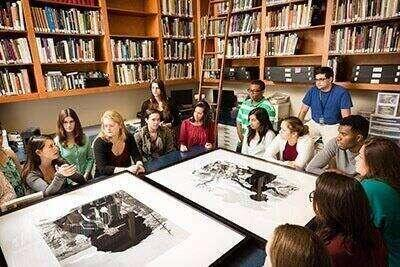 Students gather around and discuss large black-and-white photos.