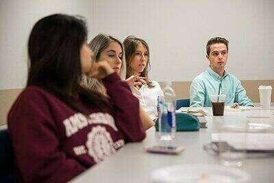 Students sit around a table at a seminar.