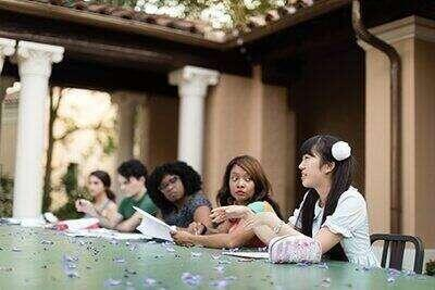 English students have class outdoors on the Rollins campus.
