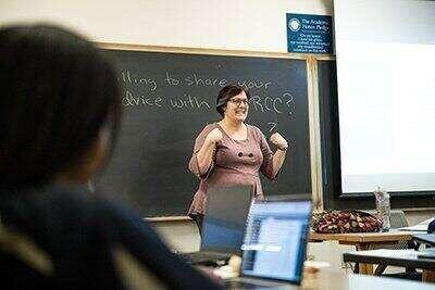 A professor presents to students at a chalkboard.