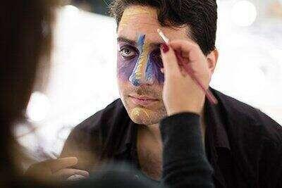 A man gets his face painted.