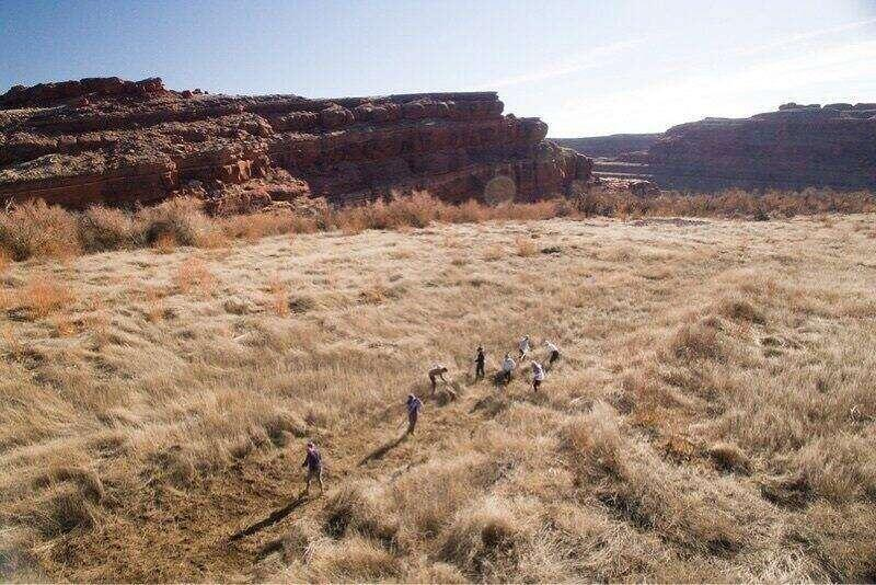 A group of students walking and studying a desert mesa.