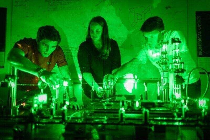 Rollins liberal arts students performing optics experiments in a lab, lit bright green.