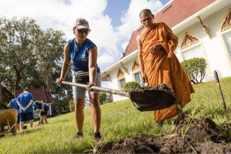 A buddhist monk with volunteers working outside.