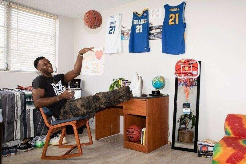 A student athlete shoots a basketball while relaxing in his dorm.