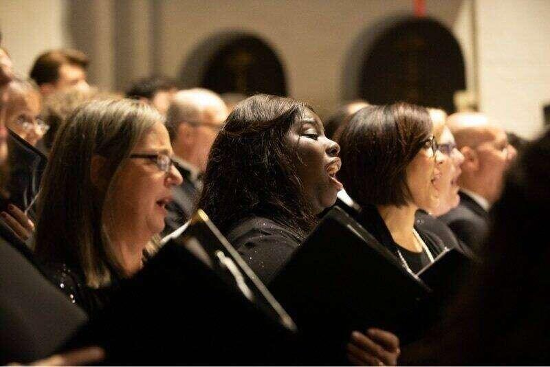 Choir members singing during a performance on campus.