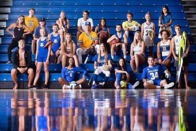 A group photo of Rollins student athletes representing each sport while sitting in the gym bleachers.