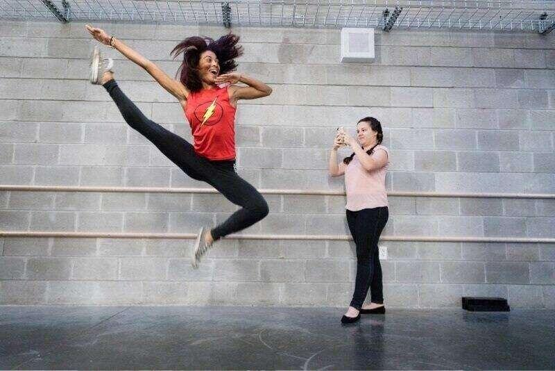 A dance student records her friend leaping in the air touching her toe.