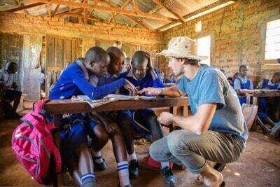 A study abroad student is kneeling at a desk teaching a group of children at a school in Africa.