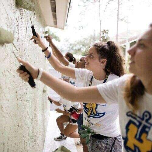 Rollins students volunteer to paint a wall.