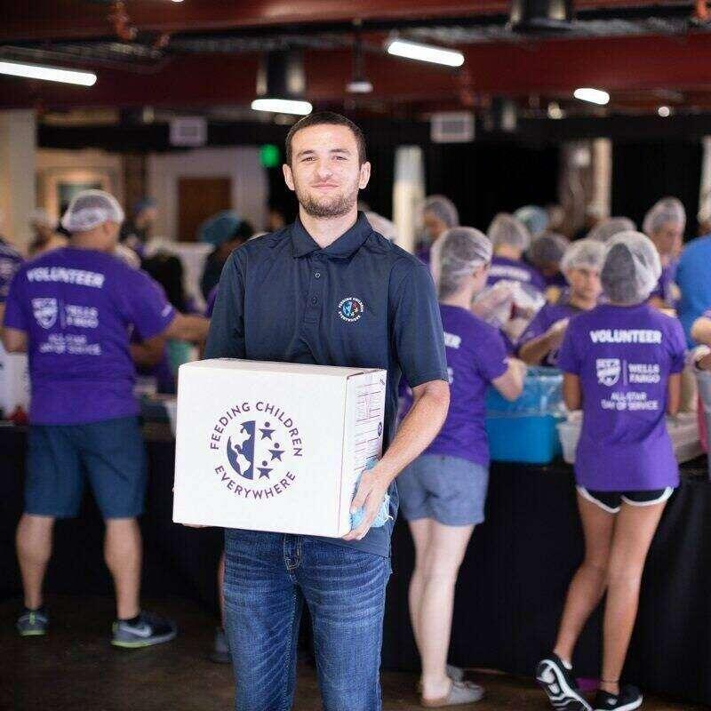 A volunteer holds a box of food as part of volunteering for a food drive