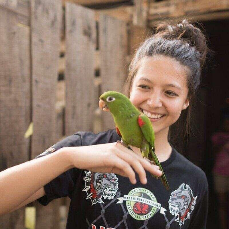 A student holding a parrot on a study abroad trip.