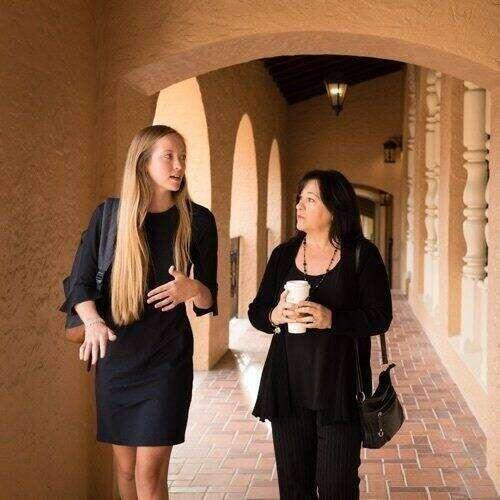 A student walking and talking with their advisor while holding coffee.
