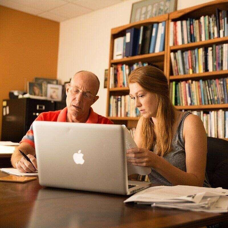 An American Studies professor and a student sitting at a laptop together and editing a paper.