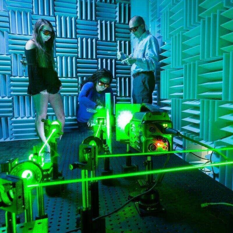 A student and a professor work in a lab with lasers.