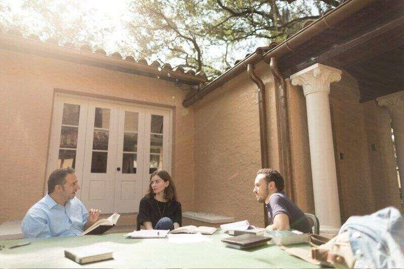 Rollins liberal arts students meet with their faculty mentor in the outdoor classroom on the Rollins campus.
