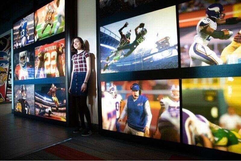 A Rollins college alumnus at EA sports offices standing in front of a wall of large monitors showing clips of football games.