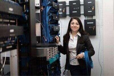 An alumn working on a bay of servers.