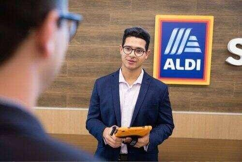 Tamer Elkhouly standing in front of a wall hung Aldi logo.